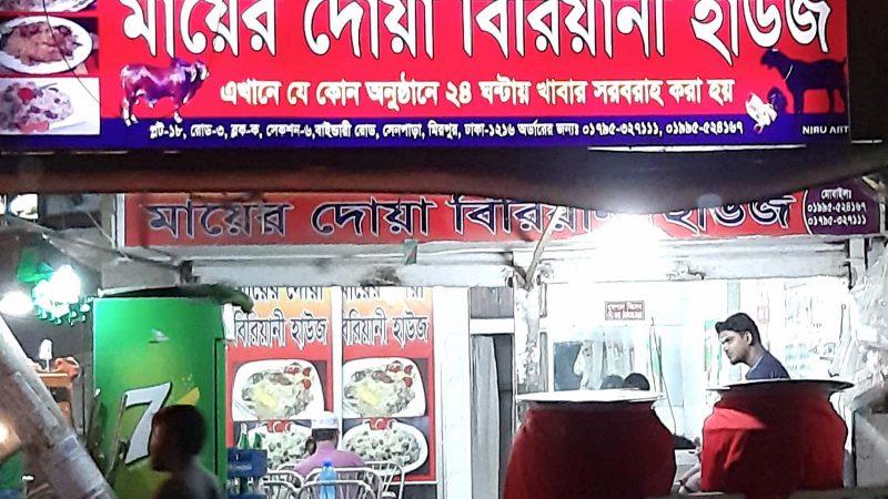 Echoppe servant du biriyani à Dhaka. Le magasin est couvert d'écriteaux en bangla, et de photos montrant les plats disponibles.