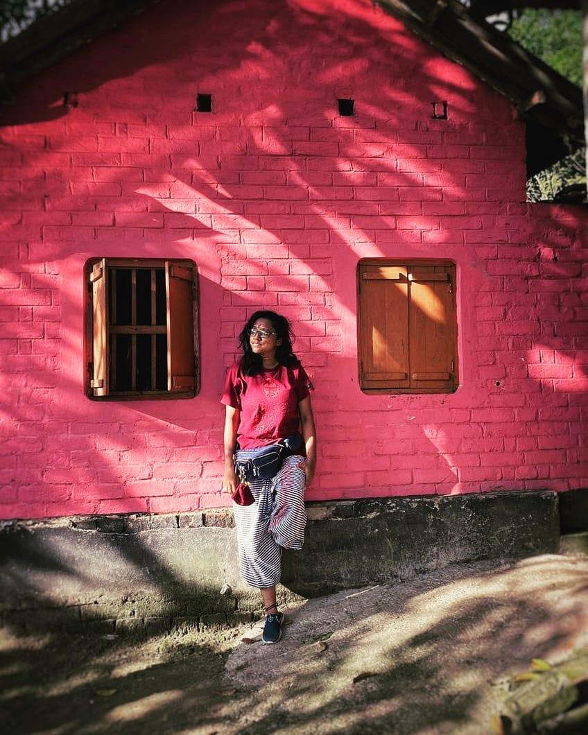 L'image montre une jeune femme adossée contre le mur d'une maison. Brune, elle porte des lunettes et son regard est tourné sur le côté. Elle est vêtue d'un t-shirt rouge et d'un pantalon bouffant rayé, noir et blanc. Elle porte autour de la taille un sac banane sur lequel est accrochée une petite bourse. En baskets, elle a un pied posé contre le mur. La maison est de couleur rose et a 2 fenêtres, l'une est ouverte et l'autre fermée. Les volets sont de couleur marron. La photographie est prise de jour, à l'ombre de la verdure avec quelques reflets de soleil.